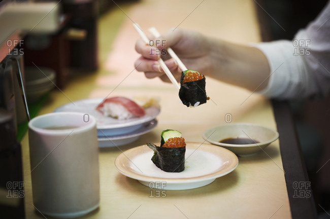 High angle close up of person eating in a sushi bar, with sushi train, Kaiten-zushi