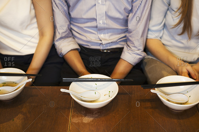 High angle close up of three people sitting side by side at a table in a restaurant, empty bowls with chopsticks in front of them