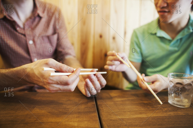 Two people, a Japanese man showing a Western man how to use chopsticks in a noodle shop