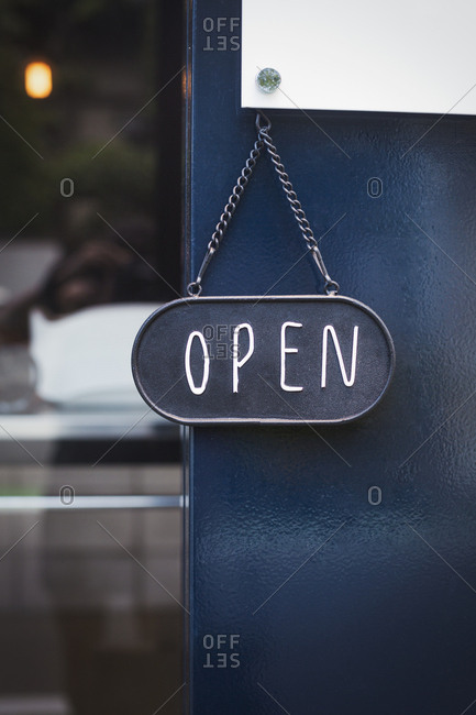 Close up of open sign on glass door to a bakery