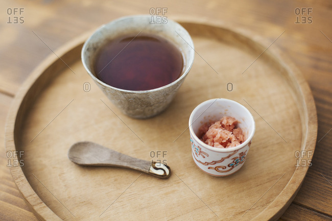 High angle close up of bowl of miso soup, bowl of crushed ginger and spoon on a wooden tray