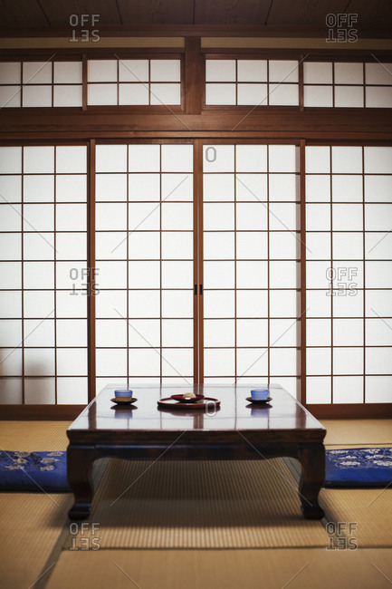 Traditional Japanese interior with low table set with bowls of tea