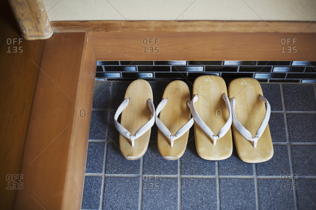 High angle view of two pairs of traditional Japanese sandals on a blue tiled floor