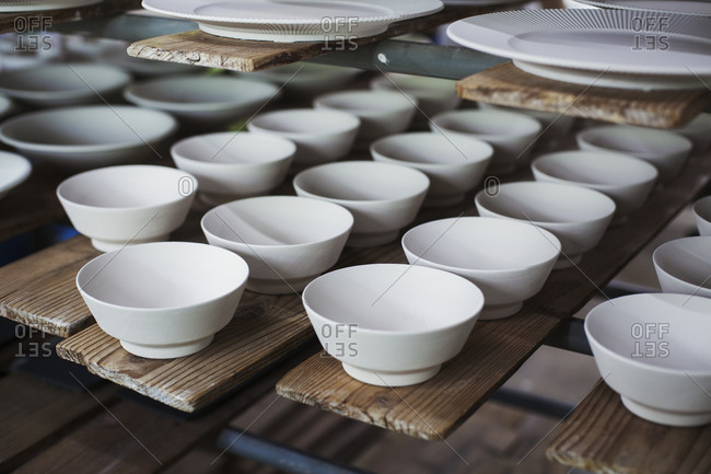High angle close up of white bowls and plates in a Japanese porcelain workshop