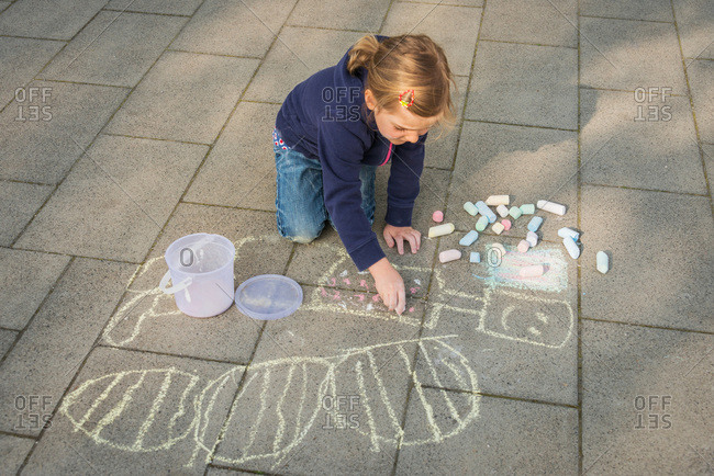 Blonde girl drawing with chalk on sidewalk, Munich, Bavaria, Germany