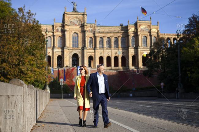 Senior couple walking against Maximilianeum, Munich, Bavaria, Germany