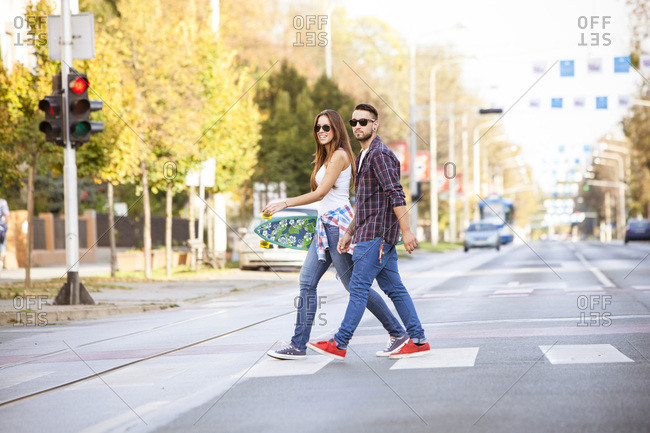 Young couple with skateboard crossing city street