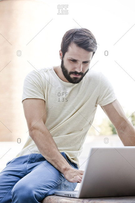 Male university student using laptop outdoors