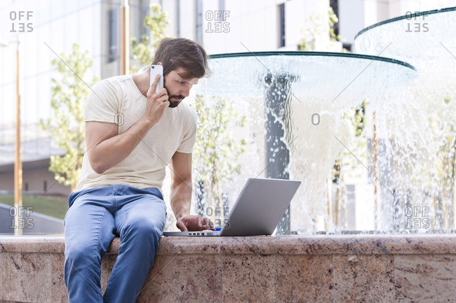 Male university student using mobile phone and laptop