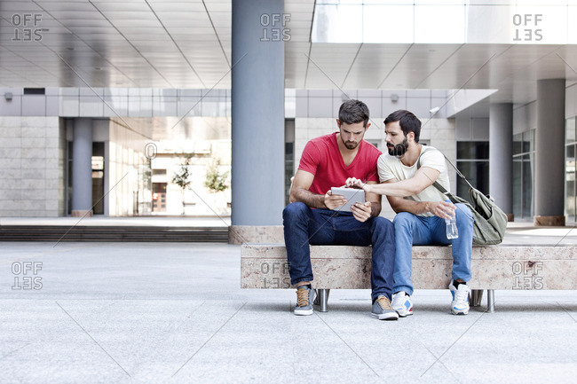 Two male university students using digital tablet on campus