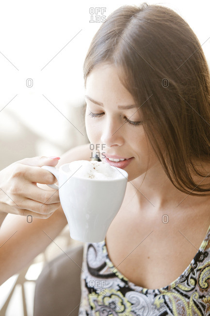 Young woman with brown hair having a cappuccino