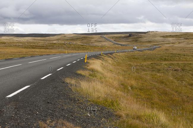 Car on highway through prairie, Iceland