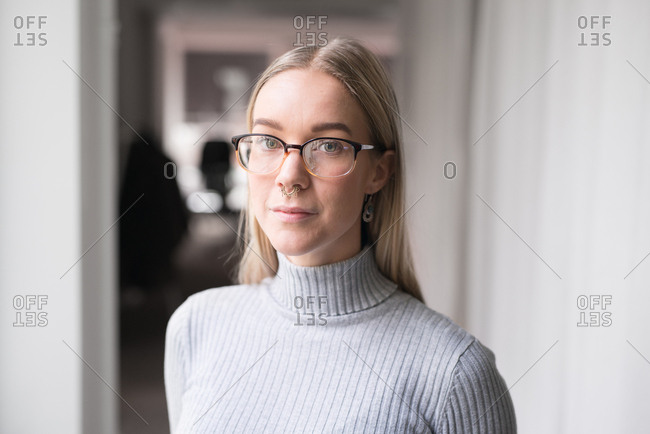 Portrait of young blonde woman with glasses and nose piercing