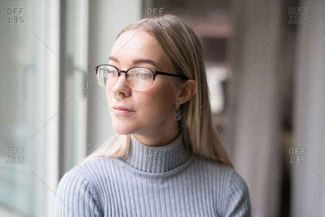 Portrait of young woman with glasses and nose piercing