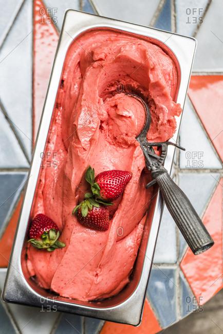 Strawberry Gelato with ice cream scooper on tile table