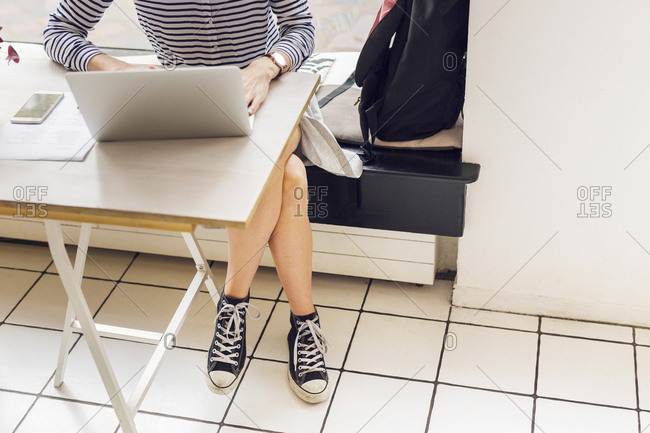 Low section of woman using laptop in cafe