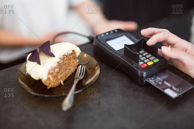 Woman paying for cake with credit card