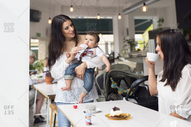 Mother holding baby son (6-11 months) and talking with friend in cafe