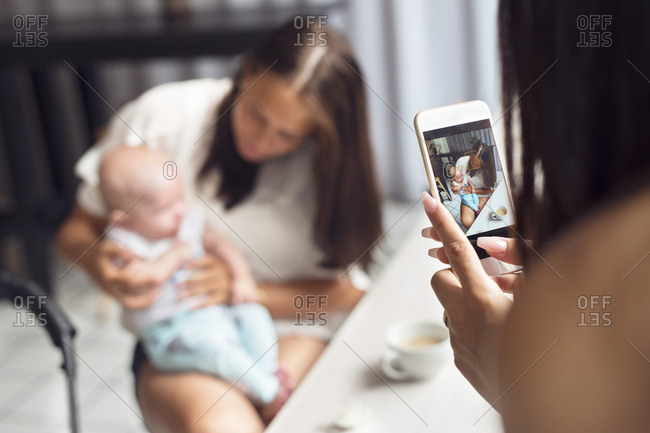 Woman photographing mother with baby son (2-5 months) in cafe