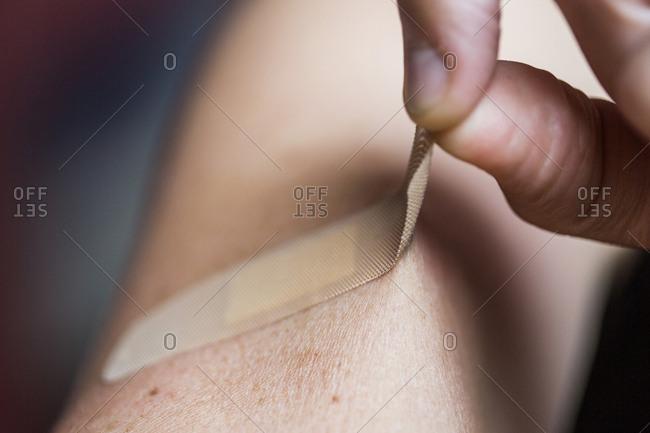 Close-up of man removing bandage