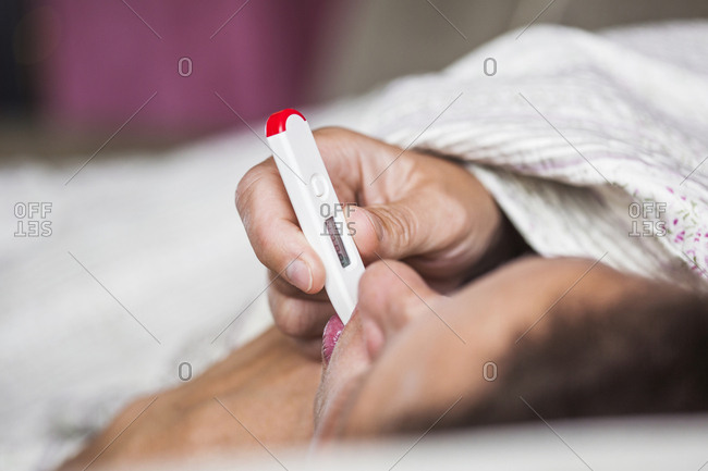 Ill woman lying down with thermometer in mouth