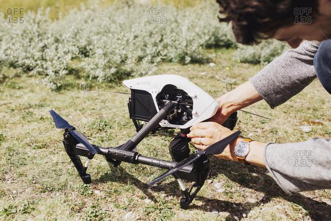 Man adjusting drone on field