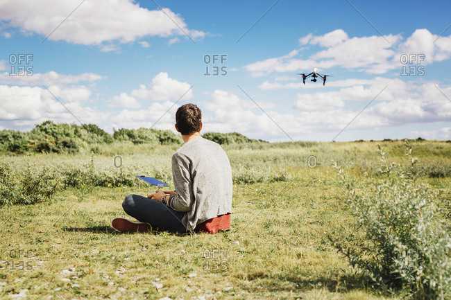 Man flying drone using remote control