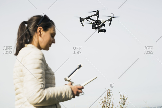 Woman flying drone using remote control