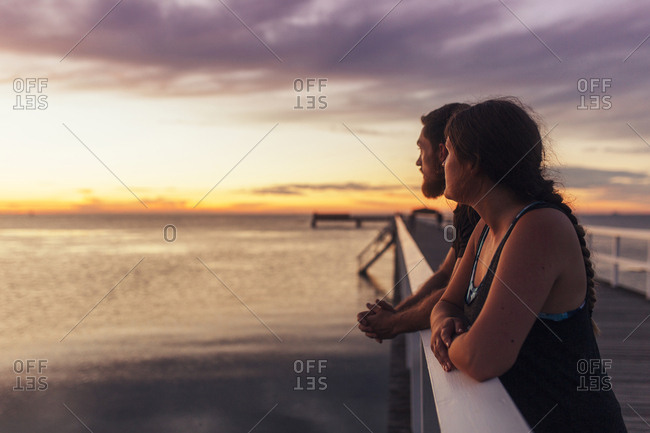 Young couple on pier at sunset