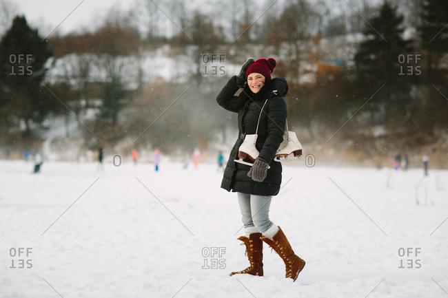 Cheerful woman with ice skates over a shoulder holding her hat in the strong winds