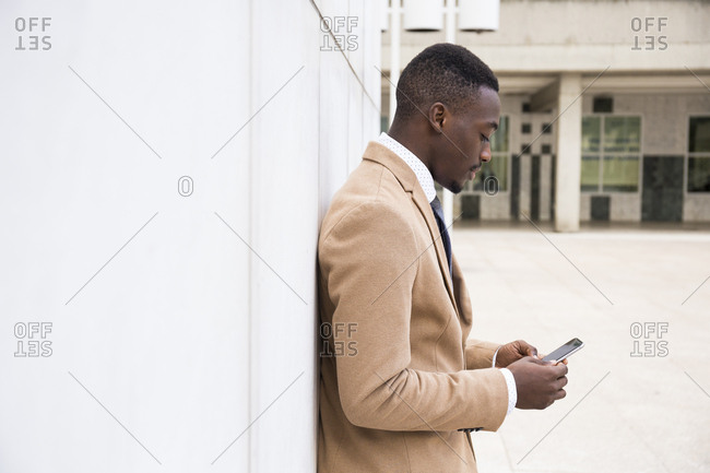 Profile view of young man using smartphone