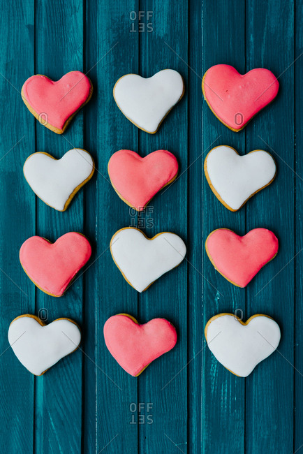 Pattern out of pink and white heart-shaped gingerbread cookies on blue wooden background