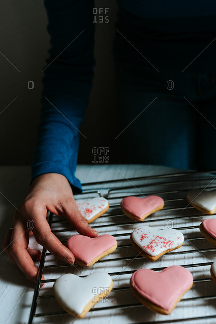 Hands holding one heart-shaped gingerbread cookie