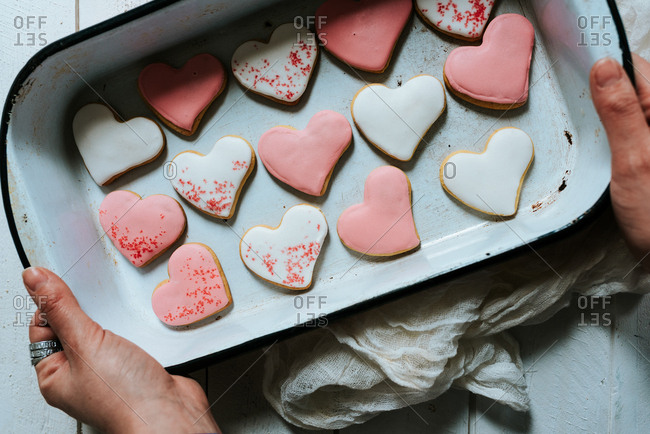 White and pink heart-shaped gingerbread cookies placed in baking tray on white background creating pattern