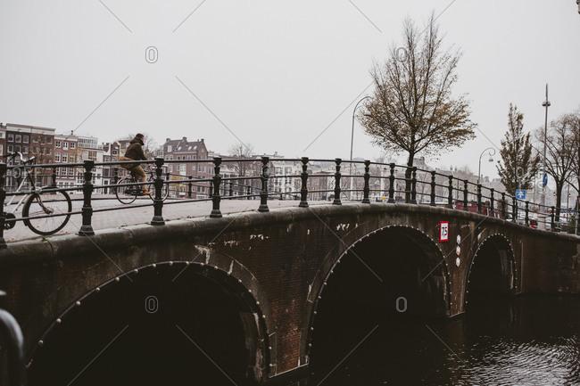 Amsterdam, Netherlands - November 16,2017: Person riding bike over Amsterdam canal bridge