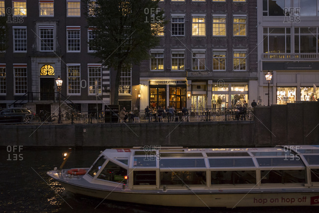 Amsterdam, Netherlands - October 28, 2016: Canal boat passing along Herengracht at dusk