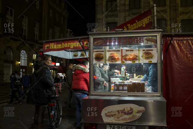 Amsterdam, Netherlands - October 28, 2016: Customers at a fast food stall at night