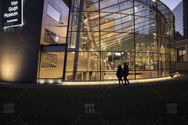 Amsterdam, Netherlands - October 29, 2016: Couple standing outside the Van Gogh Museum at dusk