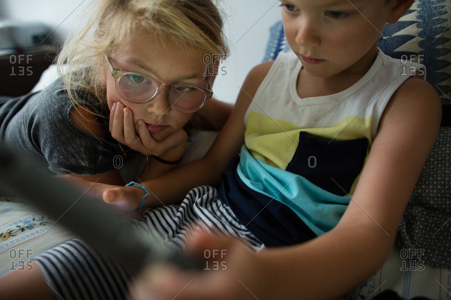 Close up of brother and sister looking at tablet