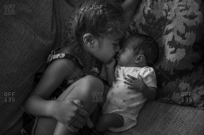 Young girl giving infant sister eskimo kiss