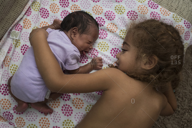 Young girl lying next to and hugging infant sister
