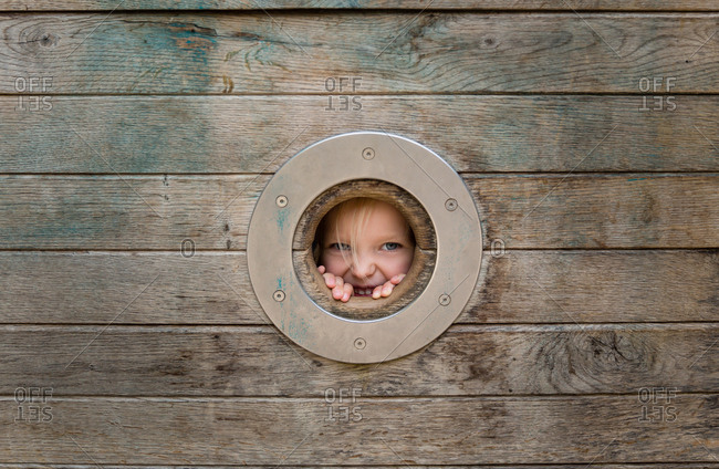 Toddler girl looking through hole on wooden structure at a playground