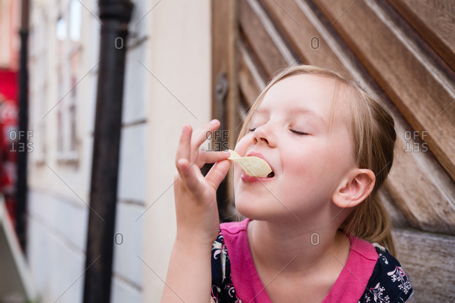 Little girl eating a chip