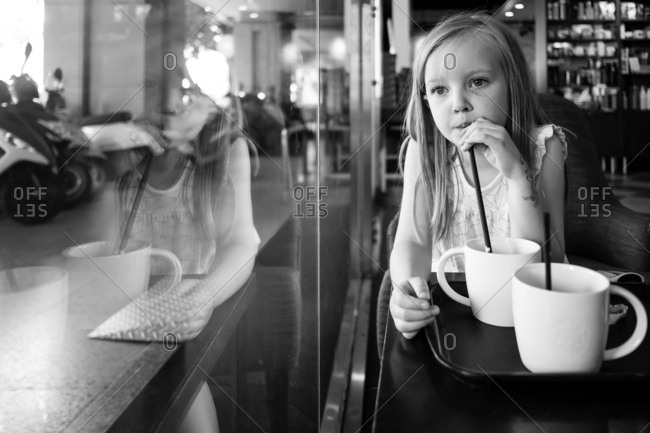 Child drinking from a cup with a straw in black and white
