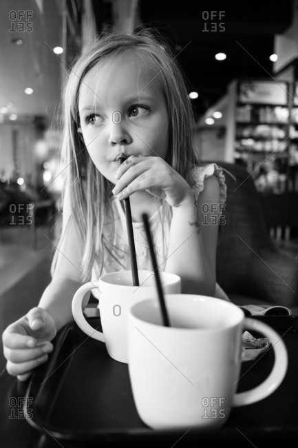 Child drinking from a mug with a straw in black and white