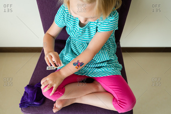Little girl putting on temporary tattoos
