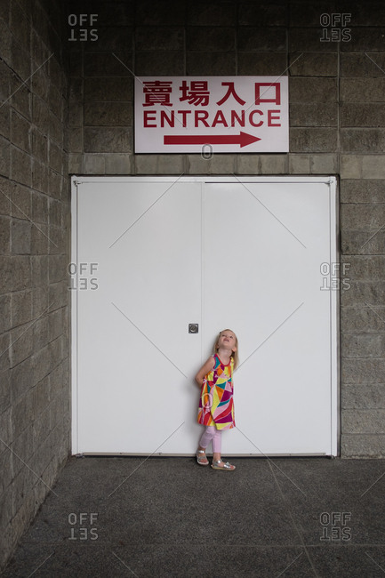 Little girl standing under door with an entrance sign and arrow