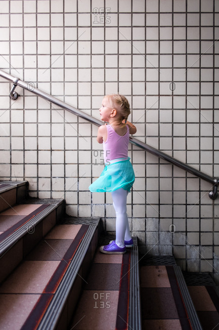 Girl in ballet outfit walking up stairs