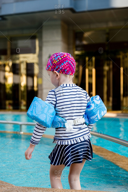 Rear view of little girl getting into a pool wearing colorful floaties