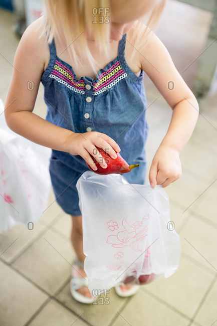 Girl putting a red pear into a bag at the grocery store